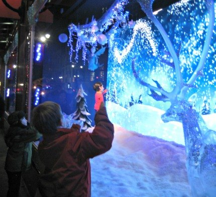 In one interactive Macy's window, kids can manipulate the swirling snowflakes by waving their arms