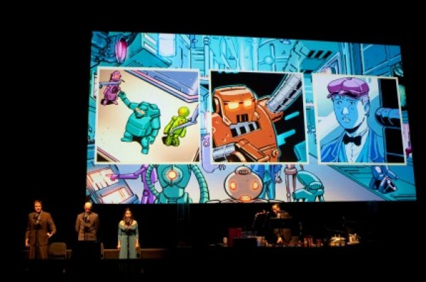 Simultaneously, comic book panels projected on a giant screen tell the story visually; photo by Robot Planet