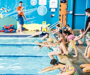 Kids dive into the pool during Goldfish Swim School's swimming classes for kids