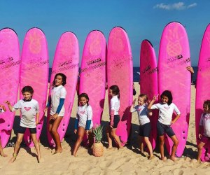 Birthday party goers pose in front of Pink Pineapple Surfboards