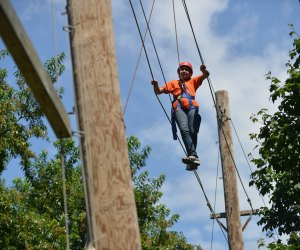 A visitor walks the high rope at Alley Pond Adventure Course