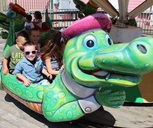 Smiling preschoolers ride the alligator at Jenkinson's
