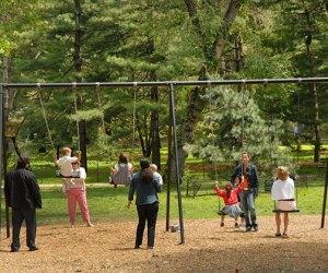 Children swing at the Arthur Ross Pinetum
