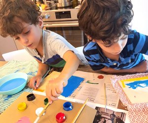 two kids boys painting at a kitchen table