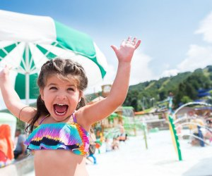 excited little girl throws up her arms in water park