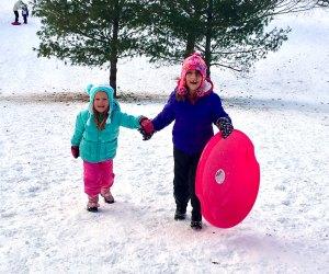 Two girls climb the sledding hill at Cedar Creek Park