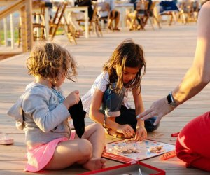 Kids playing scrabble at Collective Givernors Island