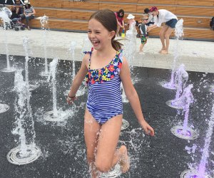 Girl runs through sprinklers at Domino Park