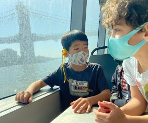 Kids gaze out the window on the NYC Ferry