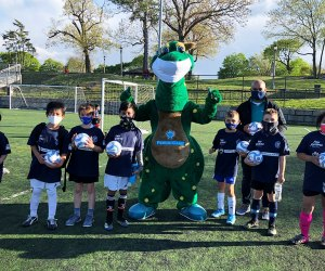kids pose with mascot on a soccer field