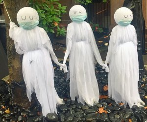 Three mask-wearing ghosts decorate a front yard