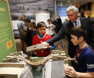 "Kevin Gover, the director of The National Museum of the American Indian, and visitors play with ""Make It, Shake It"" an interactive engineering bridge display. AP Images/Jason DeCrow for the museum"