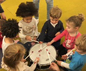 Kids bang on a drum at Groove Family Music's mommy-and-me music classes