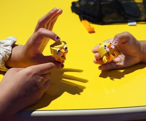 Little hands hold Lego chick creations