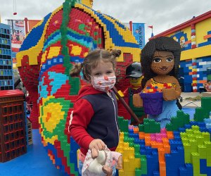 Little girl in mask poses with one of the Lego Friends