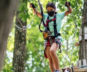 Girl in mask crosses Roap Bridge at Mountain Creek's adventure course