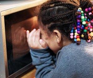 Girl peeks into microwave to check on a mug cake.