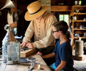 Tinsmiths show children the authentic process of transforming metal sheets into household items. Photo courtesy of Old Sturbridge Village