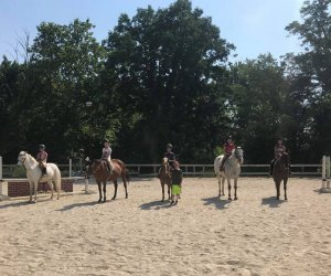 Campers get hands on riding experience at horseback riding camp. Photo from Out of Reach Farm