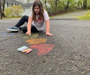girl drawing with chalk on the sidewalk