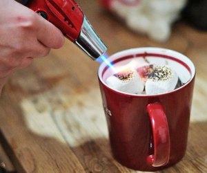 Kitchen torch toasts marshmallows atop at mug cake