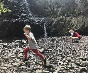 Kids frolic at the foot of a waterfall on a day trip from NYC