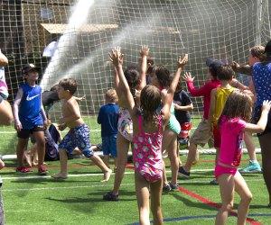Kick off your flip-flops and enjoy free outdoor play in the high-powered sprinklers at Asphalt Green's Sprinkler Day. Photo courtesy of Asphalt Green