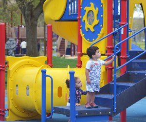 Two toddlers climb stairs on playground.
