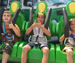 Kids strapped into an Adventureland Ride