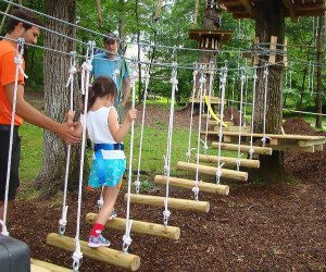 Young girl traverses low-to-the-ground rope bridge at Pocono TreeVentures