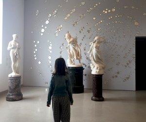 girl standing looking at sculptures