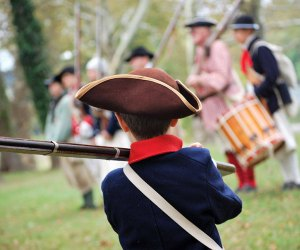 boy dressed in period costume watching a marching band