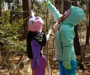 Two girls in the woods pointing at wildlife Greenburgh Nature Center Westchester winter walks