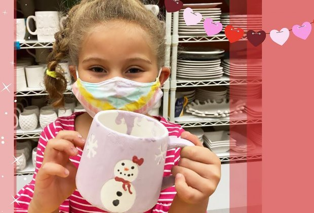 Girl holding snowman mug at arts and crafts studio Amaze In Pottery