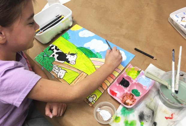 Girl paints picture of a cow