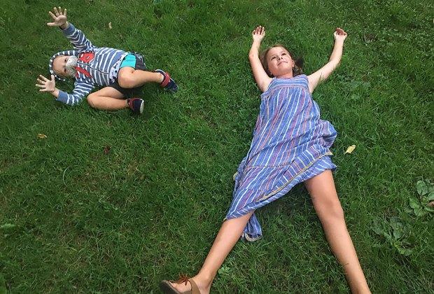 Boy and girl sprawl in grass at the Brooklyn Botanic Garden