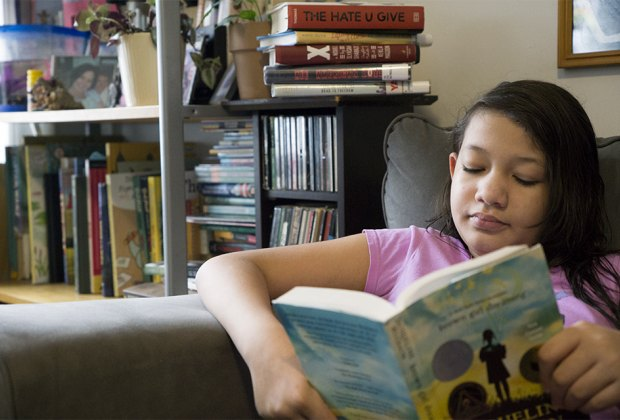 GIrl reading in chair Brown Girl Dreaming Black history for children