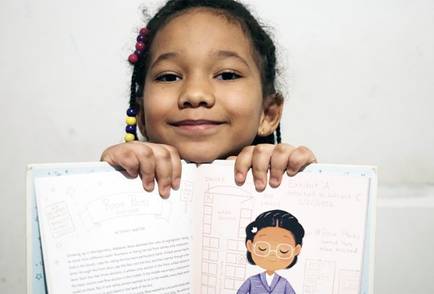 Girl holding up book black history book Ada Twist Scientist