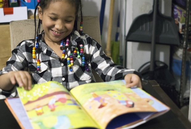 Girl smiling reading reading a black history book for children