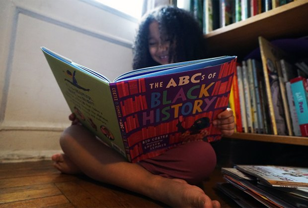 Girl smiling reading reading a black history book for children The ABCs of Black History