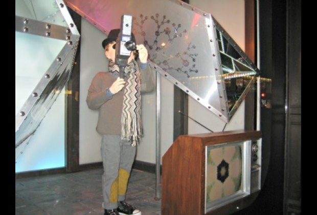 The boy's old-fashioned camera actually films spectators at Saks Fifth Avenue
