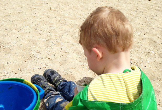 Hiking Games for Kids That Turn Walks into Adventures: kid playing in the sand with a bucket