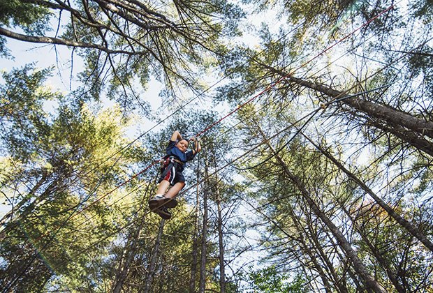 Boy walks across a tight rope at Cape May County Tree to Tree Adventure Park