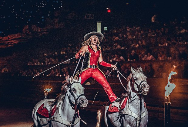woman performs a horse a show in front of an audience Dolly Parton's Stampede