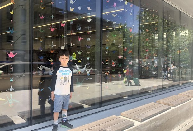Child in front of windows that are covered in artwork greenpoint library