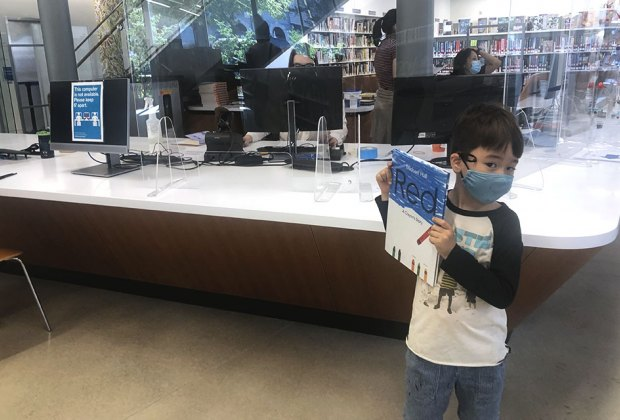 Boy holding up a book at the checkout at the greenpoint library