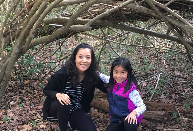 mom and daughter hiking through a woods tunnel