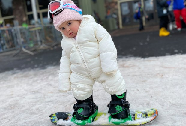 Little girl toddler snowboarding at Hunter Mountain in New York state
