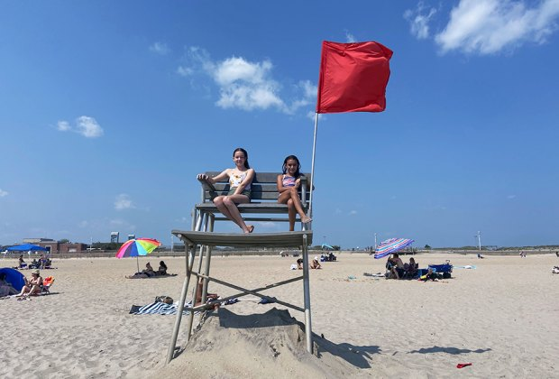 two gild in lifeguard chair at the beach