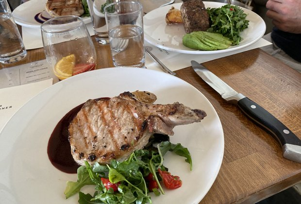 Pork chop on a plate at Three Peaks Lodge at Collective Governors Island
